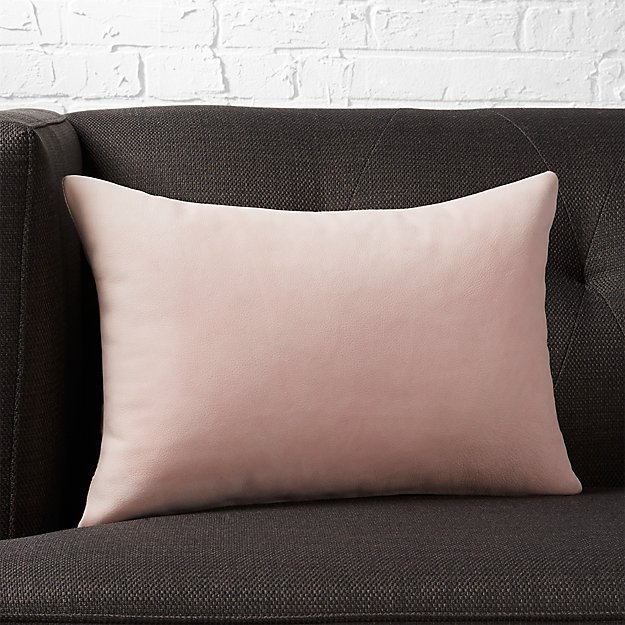 A pink pillow on a brown couch
